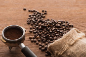 fresh roasted coffee beans and ground coffee in filter holder on wooden table