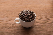 cup of fresh roasted coffee beans on wooden table