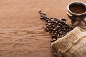 Fotografie čerstvé pražené kávové zrno a mletá káva ve filtračním držáku na dřevěném stole