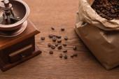 Fotografie selektivní zaměření čerstvých pražených kávových zrn v papírové tašce u mlýnku na kávu na dřevěném stole
