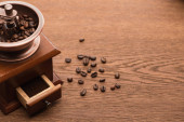 Fotografie fresh roasted coffee beans near coffee grinder on wooden table