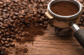 selektivní zaměření čerstvých pražených kávových zrn a mleté kávy ve filtračním držáku na dřevěném stole