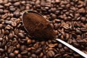 Fotografie selektivní zaměření čerstvých pražených kávových zrn a mleté kávy v lžíci