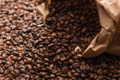 fresh roasted coffee beans scattered from paper bag