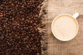 Fotografie vrchní pohled na čerstvé pražené kávové zrno a pytlovina s kávou v šálku