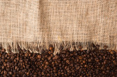 top view of fresh roasted coffee beans and sackcloth