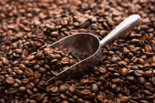fresh roasted coffee beans with metal spatula