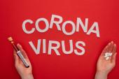 Top kilátás nő gazdaság kémcső vérmintával és tabletták közelében coronavirus felirat piros háttér
