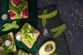 Draufsicht auf vegetarische Toasts mit frischem Gemüse auf Tuch und Steinplatte