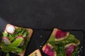 Blick auf Bio-Toasts mit Gemüse auf Steinplatte mit Pfeffer und Salz