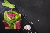 Blick auf Bio-Rettichsandwich auf Steinschneidebrett mit Pfefferkörnern und Salz