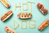 vrchní pohled na nezdravé hot dogy na modré se slovem hot dog z francouzských hranolků