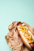 delicious hot dog with corn in paper on blue