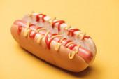 zblízka chutné hot dog s klobásou, hořčicí a kečupem na žluté