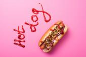 vrchní pohled na jeden hot dog na růžové se slovem hot dog napsaným kečupem