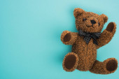 Top view of teddy bear with bow on blue background