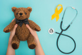 Cropped view of woman holding teddy bear near yellow awareness ribbon and stethoscope on blue background, international childhood cancer day concept