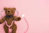 Top kilátás sztetoszkóp plüssmackó rózsaszín háttér, nemzetközi gyermekkori rák nap koncepció