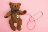 Top view of stethoscope connected with teddy bear on pink background, international childhood cancer day concept