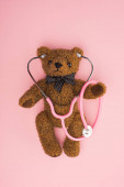 Top view of teddy bear with stethoscope on pink background, international childhood cancer day concept