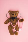 Top view teddy maci sztetoszkóppal rózsaszín háttér, nemzetközi gyermekkori rák nap koncepció
