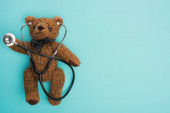 Top view of brown teddy bear with stethoscope on blue background, international childhood cancer day concept