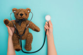 Cropped view of woman holding teddy bear with stethoscope on blue background, international childhood cancer day concept