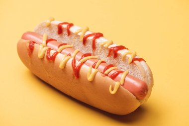 Close up of tasty hot dog with sausage, mustard and ketchup on yellow stock vector