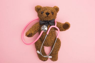Top view of stethoscope on teddy bear on pink background, international childhood cancer day concept stock vector