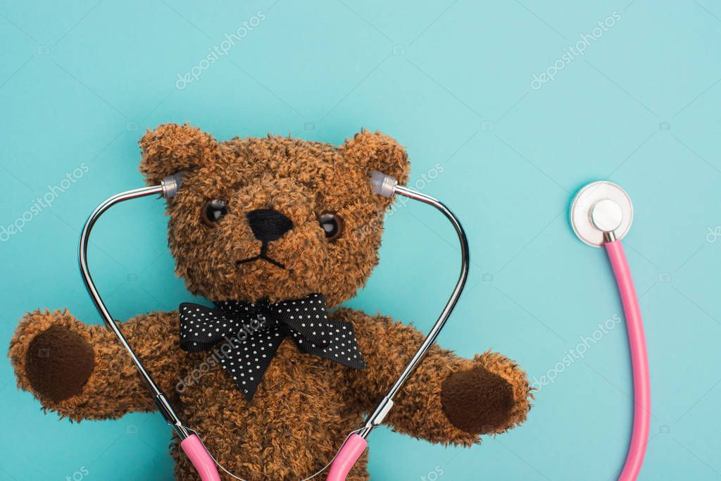 Top view of brown teddy bear with pink stethoscope on blue background, international childhood cancer day concept stock vector