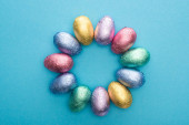 Photo Top view of circle with chocolate Easter eggs in colorful foil on blue background