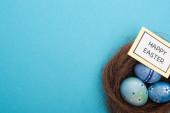 Nest von oben mit Ostereiern und Karte mit Frohe Ostern Schriftzug auf blauem Hintergrund