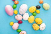 Top kilátás fényes színes édességek és húsvéti tojás kék háttér