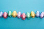 Horní pohled na čokoládové velikonoční vejce v barevné fólii na modrém pozadí