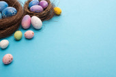 Nests with painted colorful chicken and quail eggs on blue background