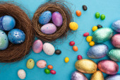 Top view of candies, chocolate Easter eggs in colorful foil near nests with painted chicken and quail eggs on blue background