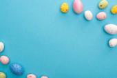 Top kilátás színes festett csirke és fürj tojás kék háttér