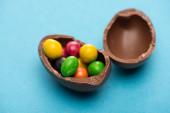 Nahaufnahme von Schokolade Ostereierhälften mit Bonbons auf blauem Hintergrund