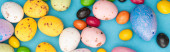 Top view of bright candies, colorful chicken and quail eggs on blue background, panoramic shot