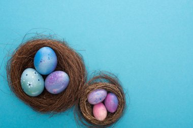 Top view of Easter eggs in nests on blue background stock vector
