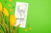 Fotografie Horní pohled na žluté tulipány, karta s jarem přichází nápisy a dekorativní srdce na zeleném pozadí