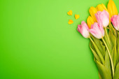 Top view of bouquet and colorful decorative hearts on green, spring concept