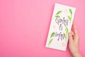 Fotografie Oříznutý pohled na ženu držící kartu s jarem přichází písmo na růžovém pozadí