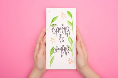 Partial view of woman holding card with spring is coming lettering on pink stock vector