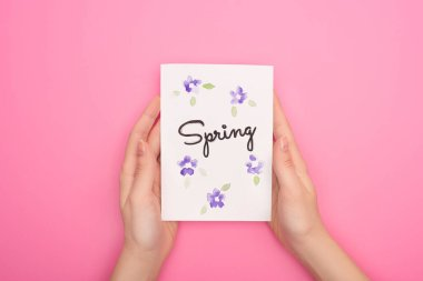 Partial view of card with spring lettering in woman hands on pink background stock vector