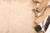 Draufsicht auf Federn, Vintage-Tasten und Kompass auf gealtertem Papier isoliert auf Weiß