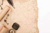 pohled shora na pírko, archivní klíče a kompas na starém papíru izolovaném na bílém