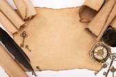 pohled shora na retro klíče, peří a kompas na stárnoucím papíru izolovaném na bílém