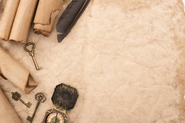 top view of vintage keys and compass near feather on aged paper