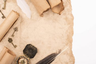 top view of feathers, vintage keys and compass on aged paper isolated on white